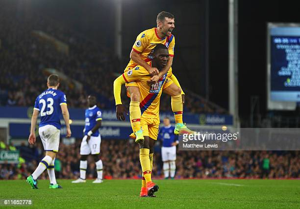 Christian Benteke of Crystal Palace celebrates with James McArthur as he scores their first goal during the Premier League match between Everton and...