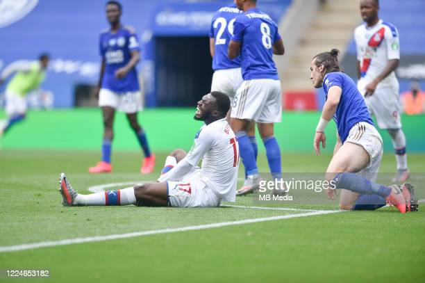 Christian Benteke of Crystal Palace goes down in pain after a challenge from Ryan Bennett of Leicester City during the Premier League match between...