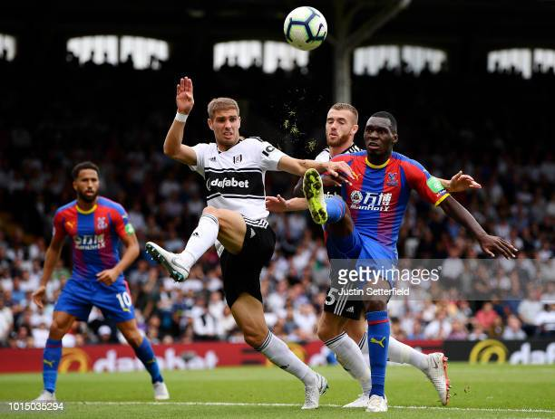 Christian Benteke of Crystal Palace is challenged by Maxime Le Marchand of Fulham and Calum Chambers of Fulham during the Premier League match...