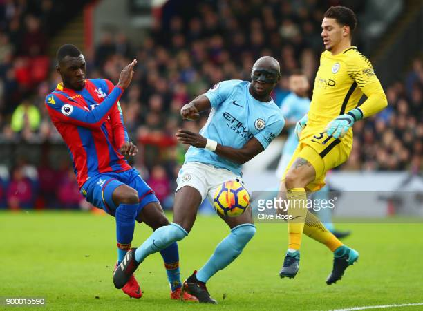 Christian Benteke of Crystal Palace is foiled by Eliaquim Mangala and Ederson of Manchester City during the Premier League match between Crystal...