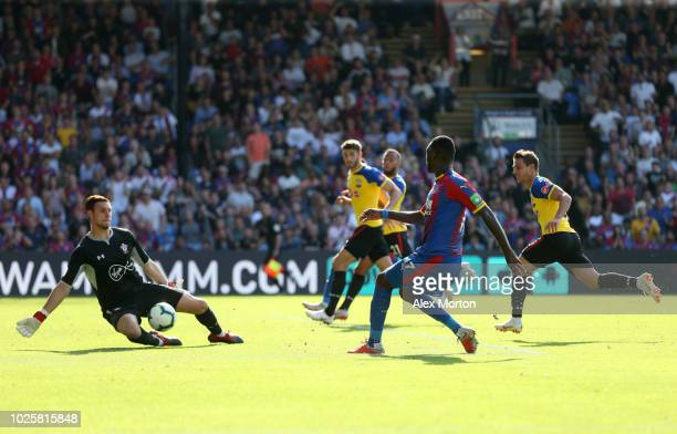 Christian Benteke of Crystal Palace shoots and misses as the ball is saved by Alex McCarthy of Southampton during the Premier League match between...