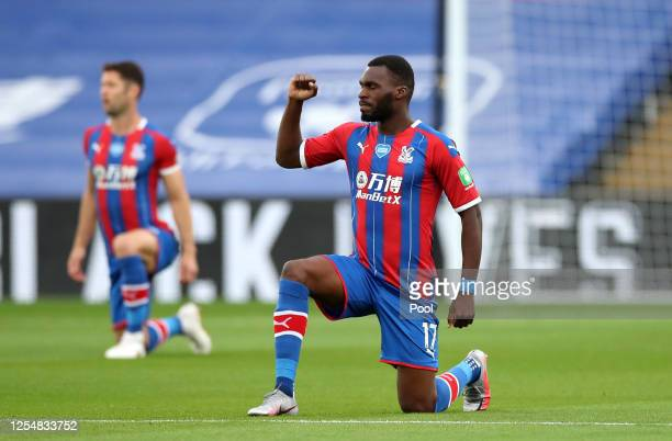 Christian Benteke of Crystal Palace takes a knee in support of the Black Lives Matter movement during the Premier League match between Crystal Palace...