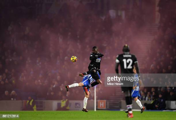 Christian Benteke of Crystal Palace wins a header as a smoke bomb goes off in the away end during the Premier League match between Brighton and Hove...