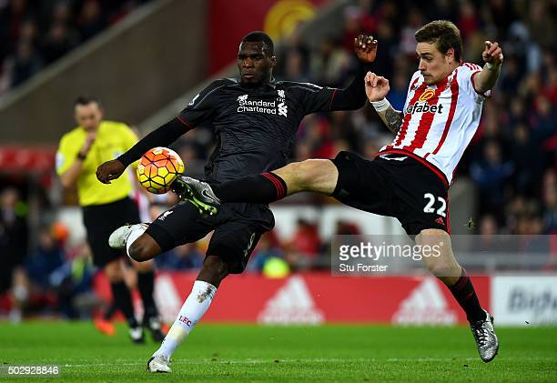 Christian Benteke of Liverpool attempts to shoot at goal under pressure from Sebastian Coates of Sunderland during the Barclays Premier League match...