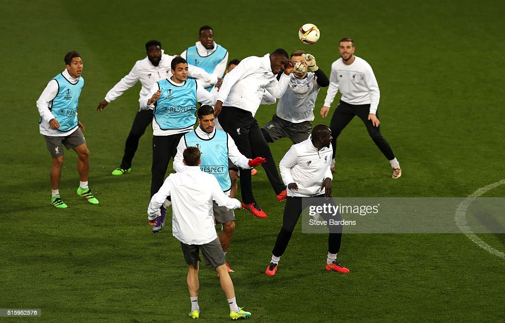 Christian Benteke of Liverpool challenges for the ball with Simon Mignolet of Liverpool during a training session ahead of the UEFA Europa League round of 16 second leg match between Manchester United and Liverpool at Old Trafford on March 16, 2016 in Manchester, England.