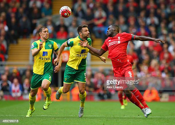 Christian Benteke of Liverpool heads the ball under pressure from Steven Whittaker and Russell Martin of Norwich City during the Barclays Premier...