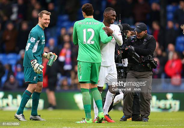 Christian Benteke of Liverpool hugs Alex McCarthy of Crystal Palace as a smiling Liverpool goalkeeper Simon Mignolet looks on after the Barclays...