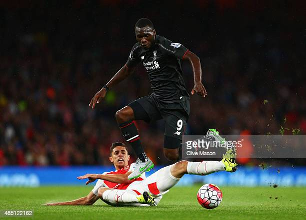 Christian Benteke of Liverpool is challenged by Gabriel Paulista of Arsenal during the Barclays Premier League match between Arsenal and Liverpool at...