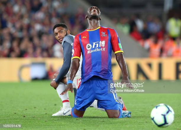 Christian Benteke of Palace screams in pain as Joseph Gomez of Liverpool tackles him from behind during the Premier League match between Crystal...
