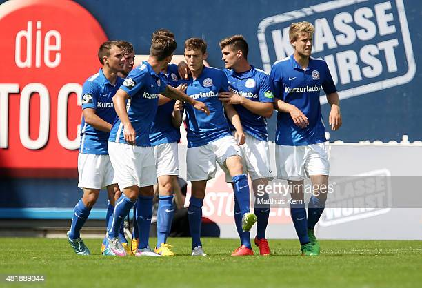 Christian Bickel of Rostock jubilates with team mates after scoring the first goal during the third league match between FC Hansa Rostock and SV...