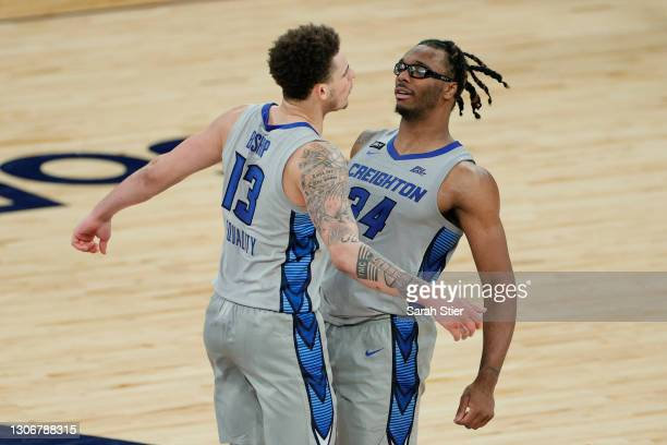 Christian Bishop celebrates with Denzel Mahoney of the Creighton Bluejays after their team's win in the second half against the Connecticut Huskies...