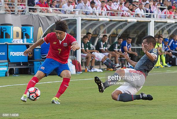 Christian Bolaños of Costa Rica crosses the ball under challenge from Miguel Samudio of Paraguay defender at the group A match between Costa Rica and...
