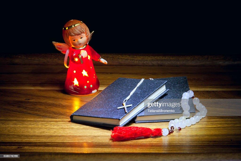 Christian books with cross, beads and  figure of an angel : Bildbanksbilder