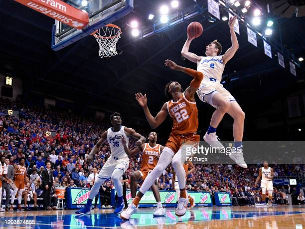 Christian Braun of the Kansas Jayhawks is fouled by Kai Jones of the Texas Longhorns as he goes up for a shot in the first half of a college...