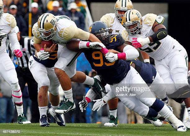 Christian Brown of the West Virginia Mountaineers tackles Bryce Petty of the Baylor Bears i the first half during the game on October 18 2014 at...