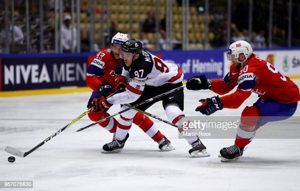 Christian Bull of Norway and Connor McDavid of Canada battle for the puck during the 2018 IIHF Ice Hockey World Championship Group B game between...