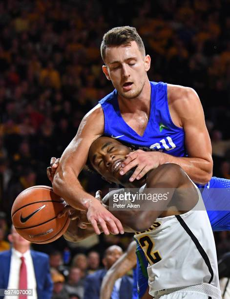 Christian Carlyle of the Florida Gulf Coast Eagles fouls Markis McDuffie of the Wichita State Shockers during the first half on December 22 2017 at...