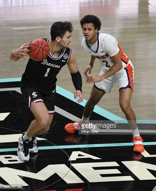 Christian Carlyle of the Santa Clara Broncos brings the ball up the court against Darryl Polk Jr. #2 of the Pepperdine Waves during the West Coast...