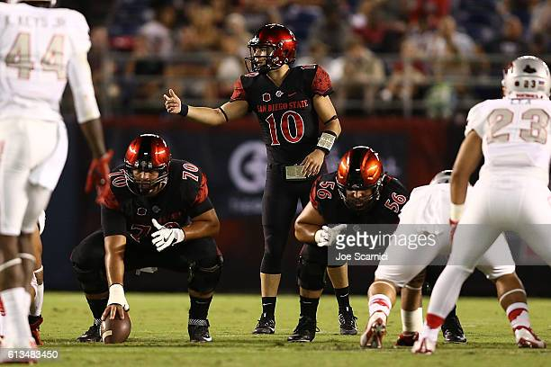 Christian Chapman of the San Diego State Aztecs makes a call from the line of scrimmage as Arthur Flores and Nico Siragusa prepare to play in the...