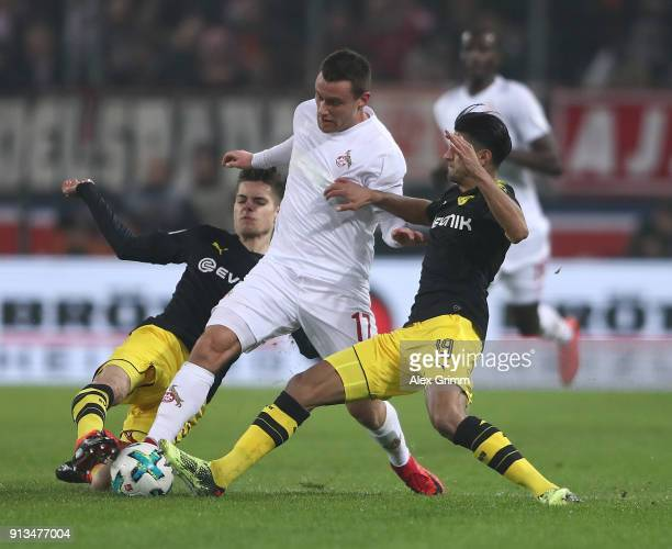 Christian Clemens of Cologne is challenged by Julian Weigl and Mahmoud Dahoud of Dortmund during the Bundesliga match between 1 FC Koeln and Borussia...
