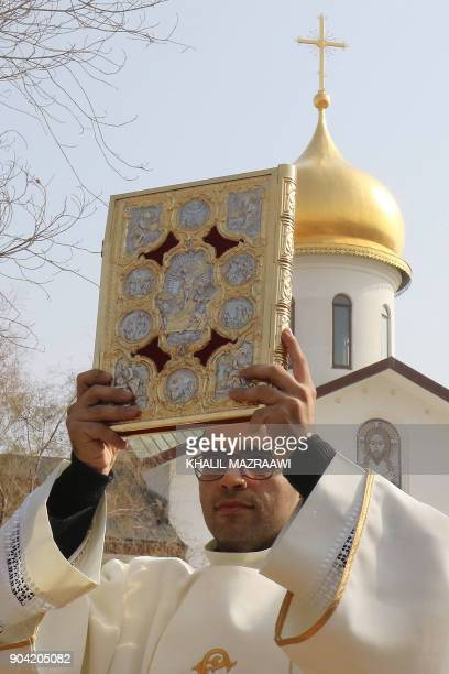 A Christian cleric holds up the bible during annual pilgrimage in Bethany beyond the Jordan river the site where many believe Jesus Christ was...