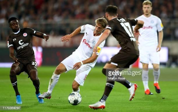 Christian Conteh of St. Pauli challenges Lion Lauberbach of Holstein Kiel during the Second Bundesliga match between FC St. Pauli and Holstein Kiel...