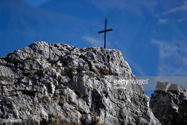 Christian cross on top of a rock. Sallanches. France.