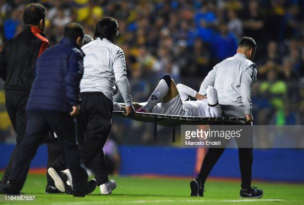 Christian Cruz of Liga Deportiva Universitaria leaves the pitch on a stretcher after suffering a serious injury on his right leg during a match...