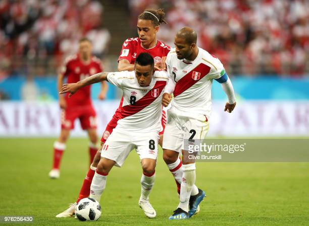 Christian Cueva and Alberto Rodriguez of Peru battle Yussuf Yurary Poulsen of Denmark for possession during the 2018 FIFA World Cup Russia group C...