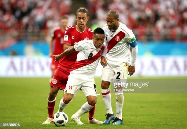 Christian Cueva and Alberto Rodriguez of Peru hold off Yussuf Yurary Poulsen of Denmark during the 2018 FIFA World Cup Russia group C match between...