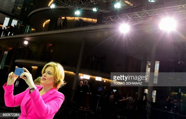 Christian Democratic Union politician an designated Minister for Food and Agriculture Julia Kloeckner takes pictures with her smartphone on March 12...