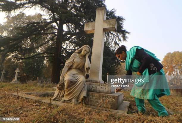 Christian devotee lights a candle during the commemoration of All Souls Day in a local cemetery in Srinagar the summer capital of Indian controlled...