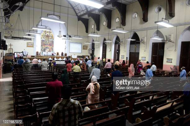 Christian devotees attend a Sunday service while maintaining social distancing at Wesley Church in Hyderabad on July 19, 2020. - Coronavirus cases in...