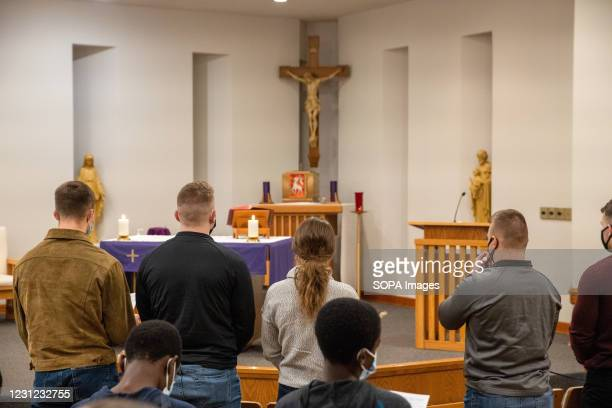 Christian devotees attend prayers at Christ the King University Parish in Athens. Father Mark Moore of Christ the King University Parish leads his...