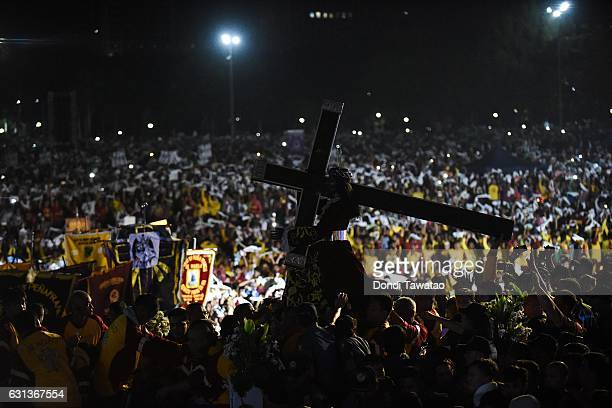 Christian devotees climb to touch the image of the Black Nazarene on January 9 2017 in Manila Philippines The Feast of the Black Nazarene culminates...