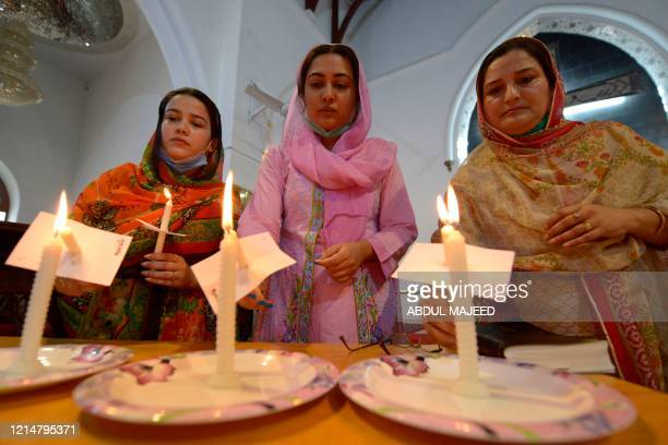 Christian devotees light candles as they pray for the victims of a plane crash during a vigil at St Johan Cathedral Church in Peshawar on May 23 a...