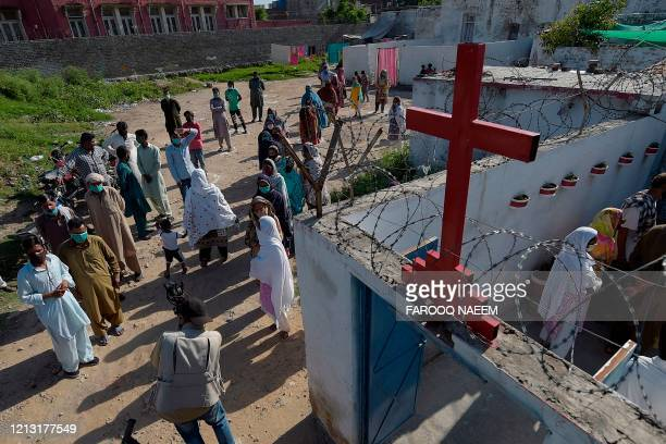 Christian devotees queue for a free food distribution outside a church after the government eased a nationwide lockdown imposed as a preventive...
