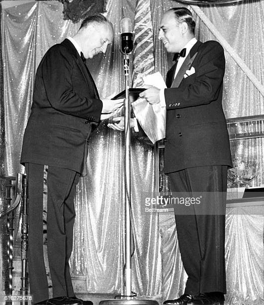 Christian Dior noted Paris fashion designer is shown as he received the 'distinguished service in the field of fashion award' from Stanley Marcus of...