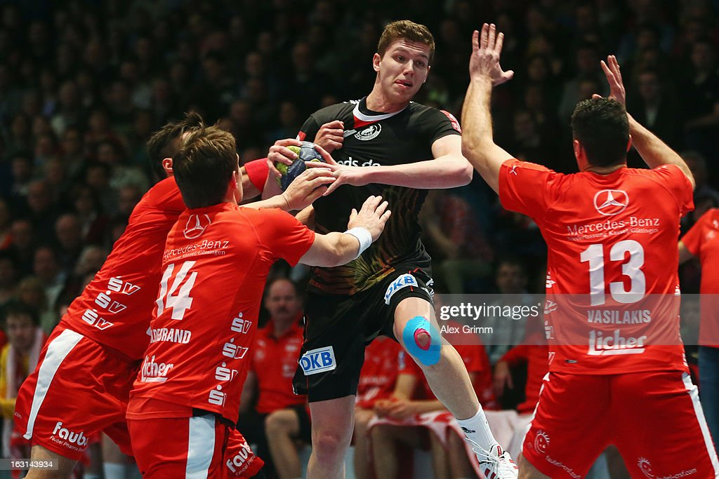 Christian Dissinger of Germany is challenged by Michael Allendorf, Christian Hildebrand and Alexandros Vasilakis (L-R) of Melsungen during a benefit match between the German national handball team and MT Melsungen at Rothenbach-Halle on March 5, 2013 in Kassel, Germany.