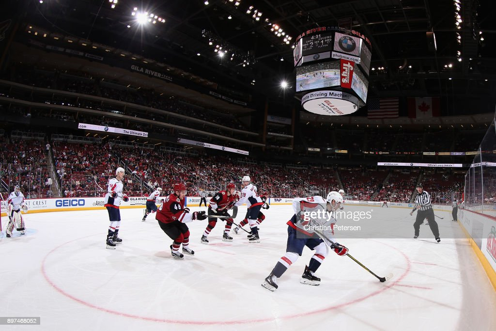 Christian Djoos #29 of the Washington Capitals skates with the puck ahead of Josh Archibald #45 of the Arizona Coyotes during the third period of the NHL game at Gila River Arena on December 22, 2017 in Glendale, Arizona. The Coyotes defeated the Capitals 3-2 in overtime.