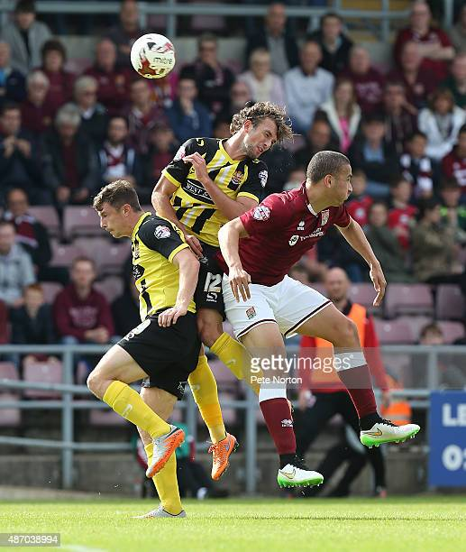 Christian Doidge and Matt McClure of Dagenham Redbridge contest the ball with Rod McDonald of Northampton Town during the Sky Bet League Two match...