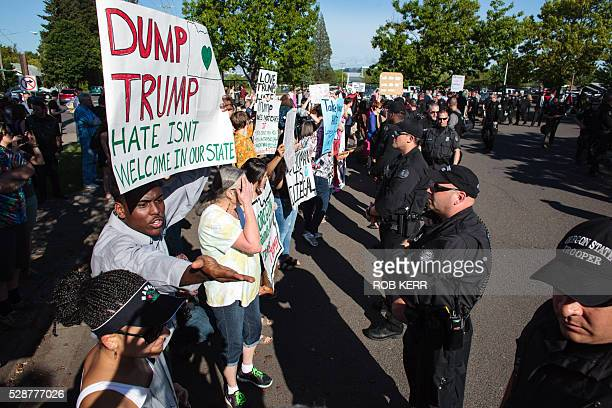 Christian DouglassDevine holding a 'Dump Trump' placard yells comments to supporters along a line of police outside of an event for US Republican...