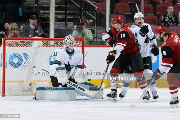 Christian Dvorak of the Arizona Coyotes attempts to redirect the puck past goalie Martin Jones of the San Jose Sharks as Dylan DeMelo of the Sharks...