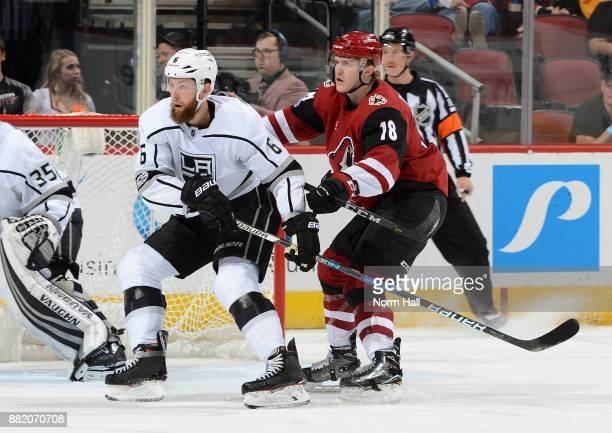 Christian Dvorak of the Arizona Coyotes battles for position with Jake Muzzin of the Los Angeles Kings at Gila River Arena on November 24 2017 in...
