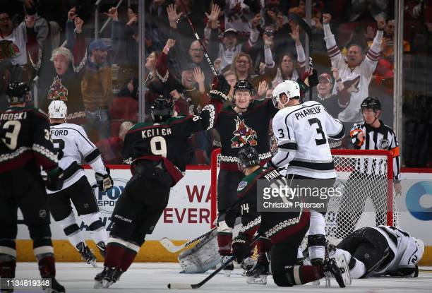 Christian Dvorak of the Arizona Coyotes celebrates with Clayton Keller after scoring a goal ahead of Dion Phaneuf and Trevor Lewis of the Los Angeles...