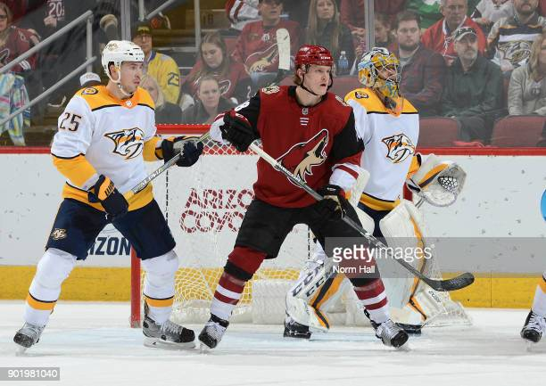 Christian Dvorak of the Arizona Coyotes looks for the puck while standing between Alexei Emelin and Juuse Saros of the Nashville Predators at Gila...