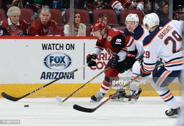 Christian Dvorak of the Arizona Coyotes skates with the puck ahead of Connor McDavid and Leon Draisaitl of the Edmonton Oilers during the first...