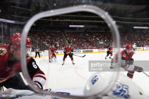 Christian Dvorak of the Arizona Coyotes watches the puck in the corner while standing in front of his own net against the Tampa Bay Lightning at Gila...