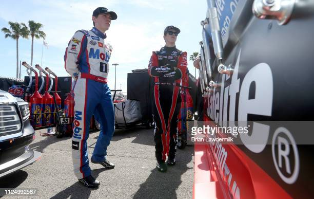 Christian Eckes driver of the SiriusXM Toyota and Harrison Burton driver of the Safelite AutoGlass Toyota talk in the garage area during practice for...