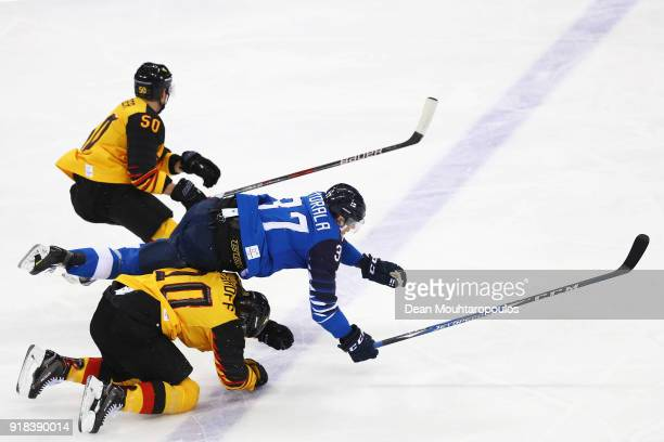 Christian Ehrhoff and Felix Schutz of Germany crash into Mika Pyorala of Finland during the Men's Ice Hockey Preliminary Round Group C game on day...